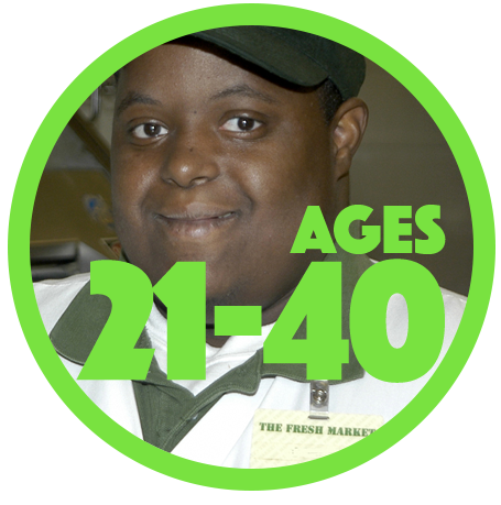 Close up of a smiling young man of color with a developmental disability who is wearing a work uniform with green cap and white polo shirt with green color. Name tag says The Fresh Market.