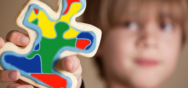 boy holding multi-colored puzzle piece in his hand