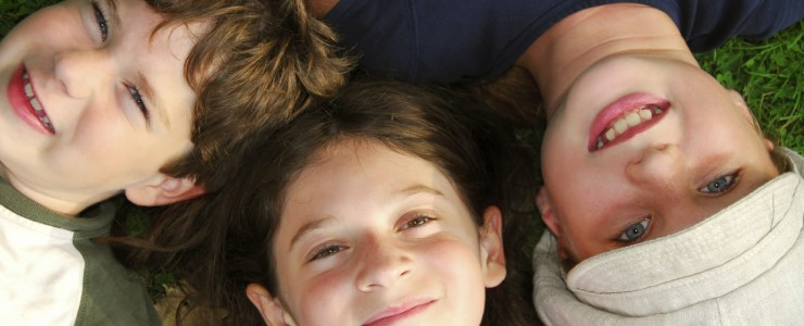 three children lying on the ground, looking up, smiling