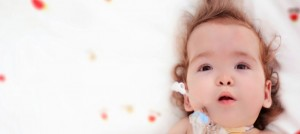 Infant with Down syndrome lying on a white blanket with red and yellow dots. Infant has a feeding tube.