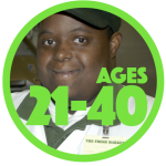 "Close up of a smiling young man of color with a developmental disability who is wearing a work uniform with green cap and white polo shirt with green color. Name tag says, ""The Fresh Market."""