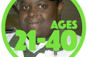 """Close up of a smiling young man of color with a developmental disability who is wearing a work uniform with green cap and white polo shirt with green color. Name tag says, """"The Fresh Market."""""""