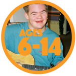 Teenage boy with Down syndrome in blue shirt, smiling, playing guitar.