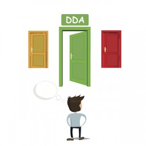 Man standing before three doors. The middle door has a sign that reads: DDA