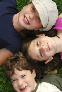 Portrait of three young children lying on grass looking up