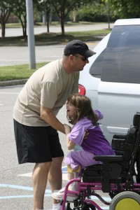 father lifting daughter out of her wheelchair, into van