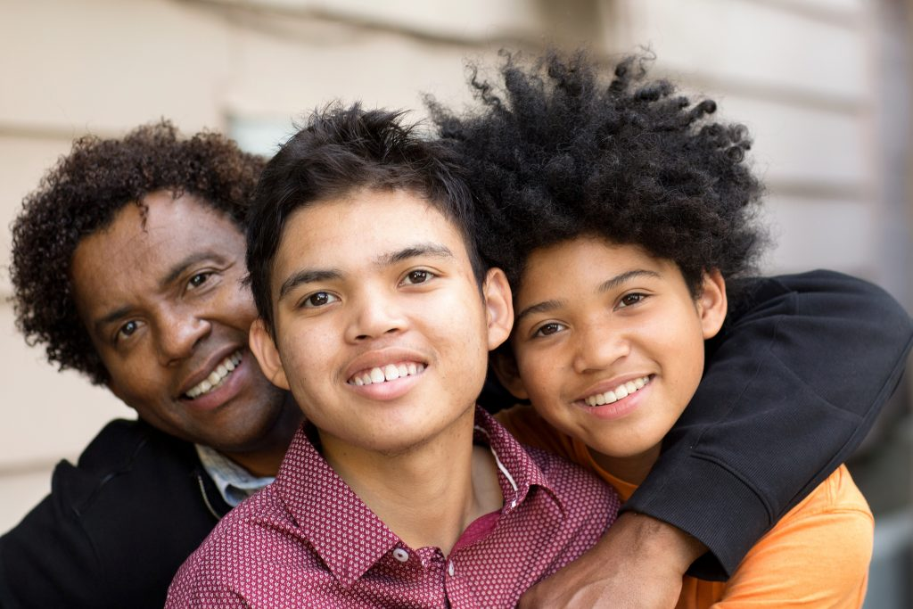 Portrait of an African American father hugging his sons.