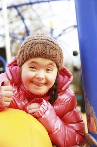 Girl with Down syndrome on swings, smiling