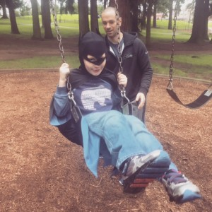 Father pushing son on a swing. Son is dressed as batman.