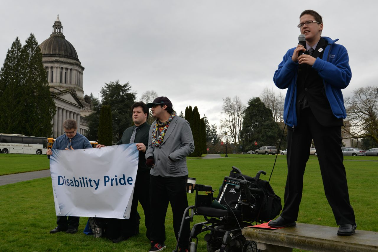 foreground: Ivanova Smith speaking at Disability Pride Rally. Background: Washinton State Capitol