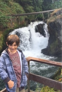 boy smiling, waterfall background