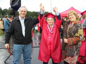 Silas in cap and gown, celebrating with his parents