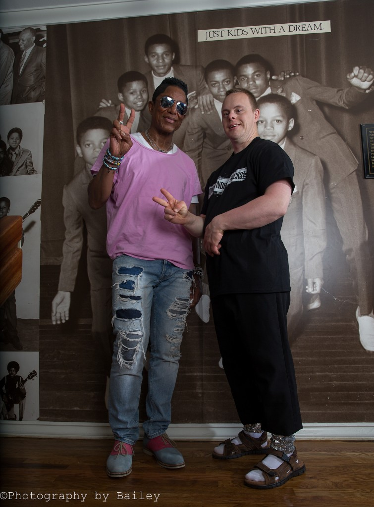 Jermaine Jackson poses with Dylan Kuehl in front of Jackson family portrait