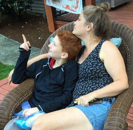 mother and son outside, sitting in a chair together