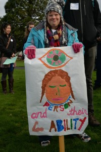 Woman at rally holds sign that reads: See the person and their ability.