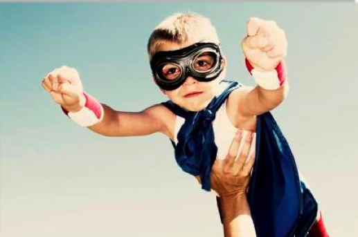 child in goggles and cape being held in the air to fly