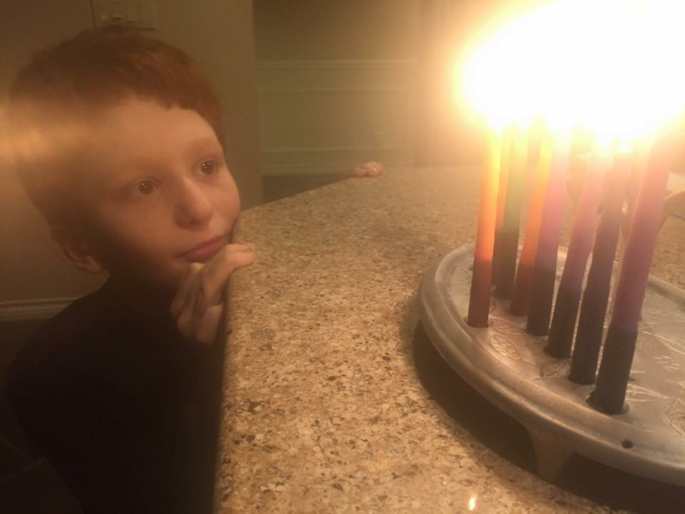 young boy and menorah