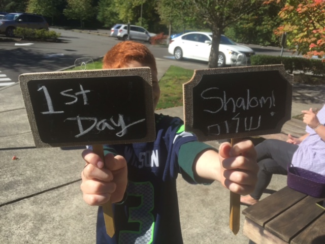 boy holds signs that read 1st Day Shalom
