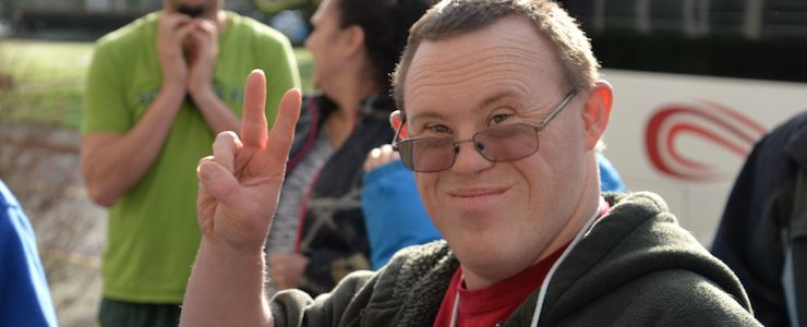 Man with Down syndrome making a peace sign.