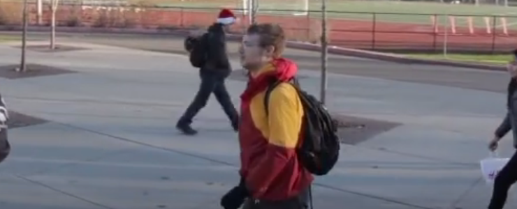 male studen with backpack walks across high school campus