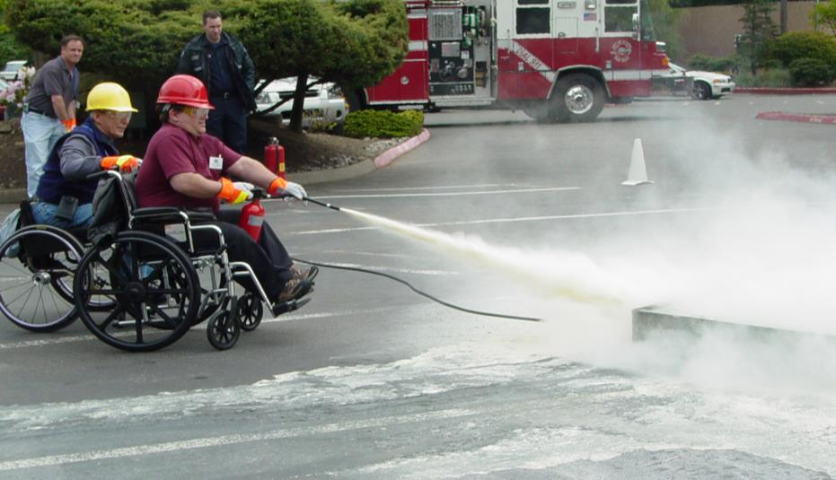 Two men in wheelchairs with hardhats and emergency vests operate a fire extinguisher on a street during a mock emergency scene. Fire truck in background.