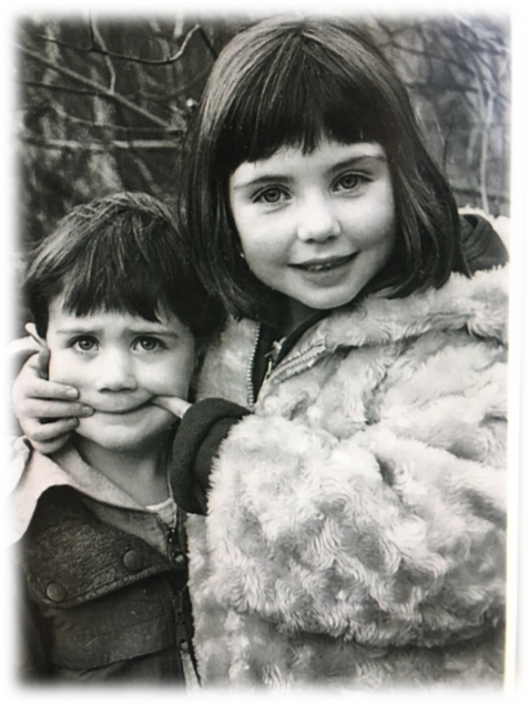 Black and white photo of a brother and sister. Sister is making a face with her hands on her brother's face.