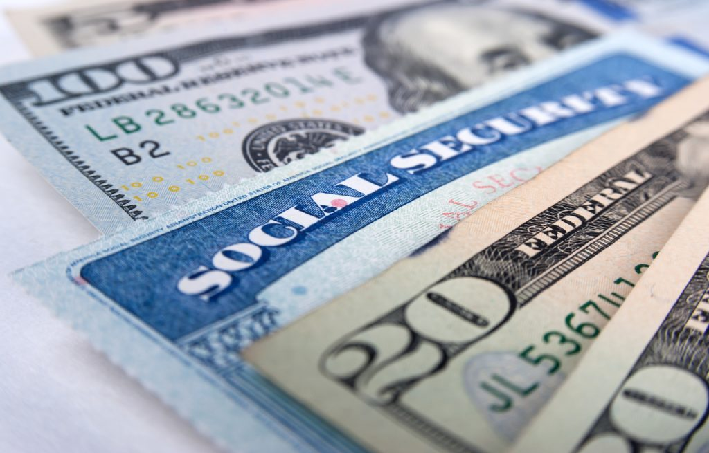 Social security card and American money dollar bills close up
