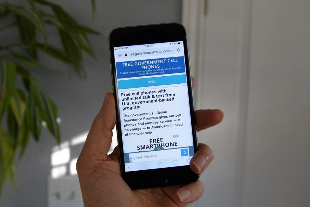 hand holding a cell phone with freegovernmentcellphones.net homepage displayed on the screen.