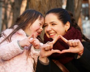 mother and daughter, smiling and making heart shapes with hands.