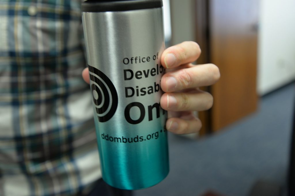 Hand holding a travel mug with Office of Developmental Disabilities logo and website url ddombuds.org
