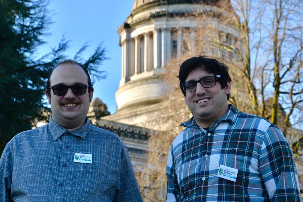 DD Ombuds staff, Tim McCue and Noah Seidel outside the state capitol building, smiling