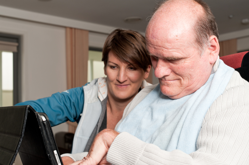 Man in a wheelchair using a laptop with assistance from a care worker.