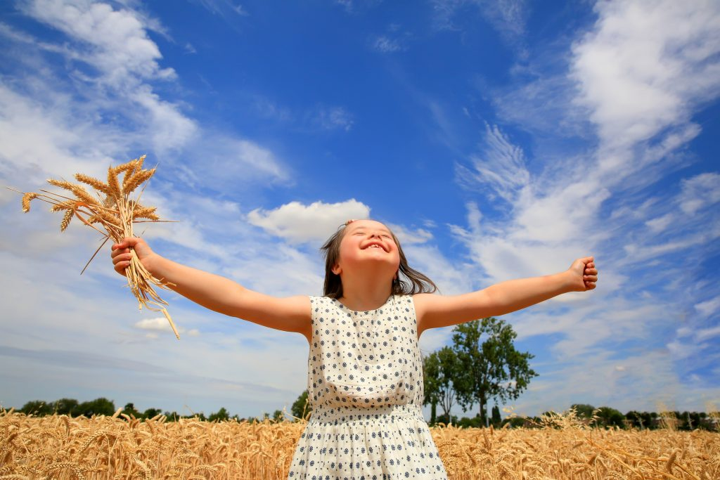Smiling young girl with Down syndrome in a wheat field with arms outstretched. Sunny, blue skies with fluffy white clouds in background.