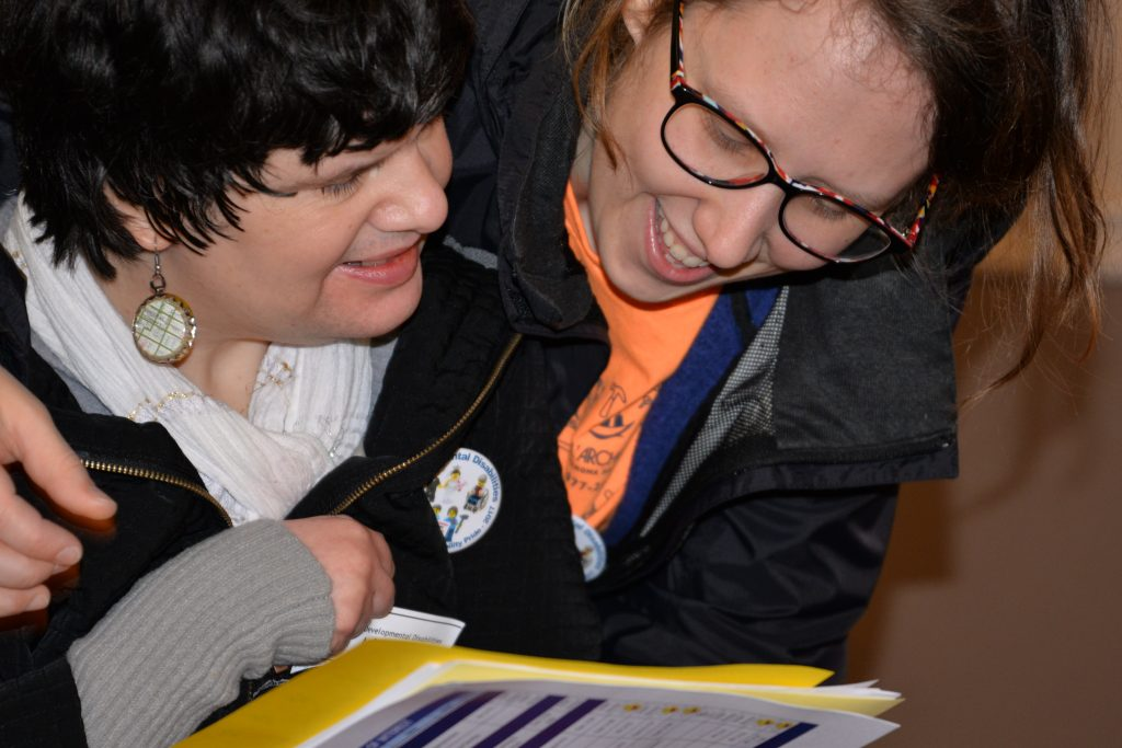 Close up picture of a woman with disabilities reading through materials with a support person.