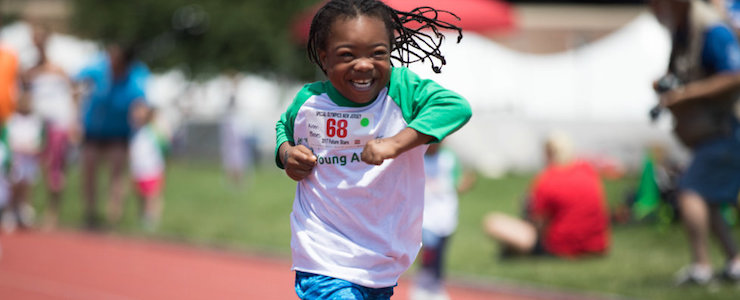 Smiling young African American athlete running on a track.