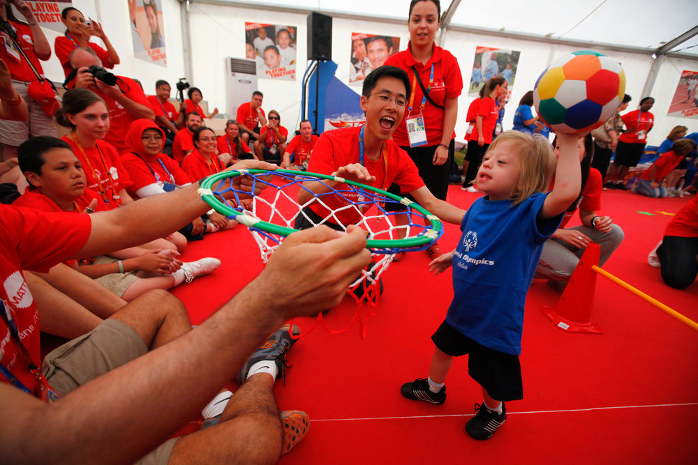 Young child, smiling, holds up a multicolored ball, poised to toss into a net held out by another person. Background with cheering atheletes in red shirts.