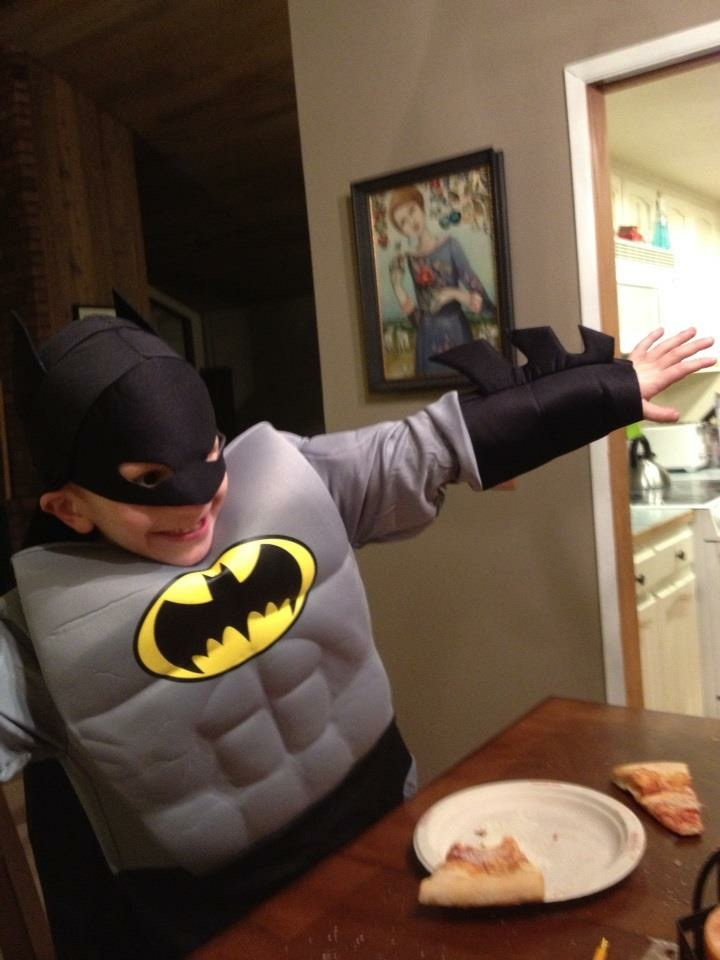 Nate in his batman costume at the family dinner table, arms outstreched like an airplane. A piece of pizza sits on a plate in front of him.