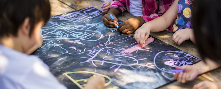 Children drawing art on chalkboard outdoors.