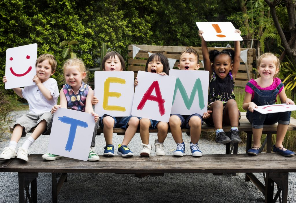 "Children are sitting on the wooden table, each holding a different colored letter of the word ""team."""