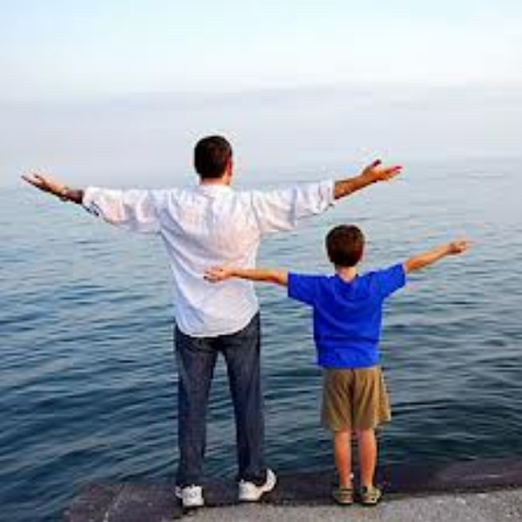 father and son with arms outstretched, facing the ocean, backs to the camera.