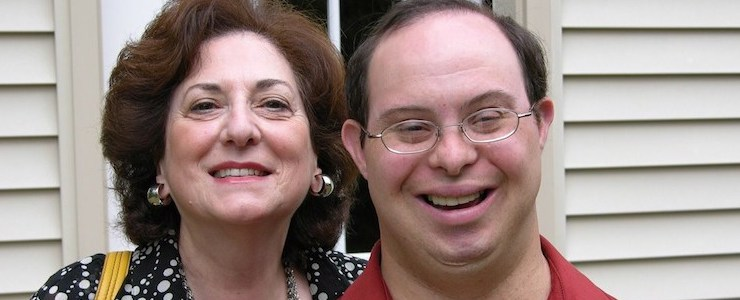 Close up of mother and adult son with Down syndrome, smiling.