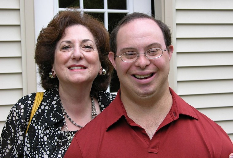 Mother and adult son with Down syndrome, smiling.