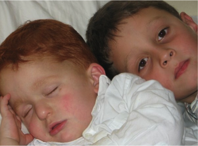 Nate as a toddler, napping alongside his older brother.