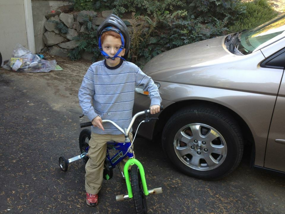 Nate on a bike, with helmet strap across his face.