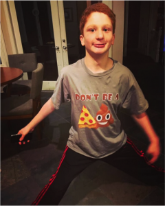 Teenager Nate mugging for the camera, wearing a t-shirt with the image of a pizza slice and poop emoji.