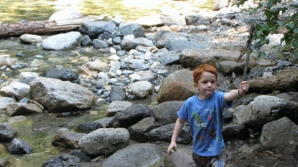 Nate as a young boy, walking along a rocky river bed, waving a stick.