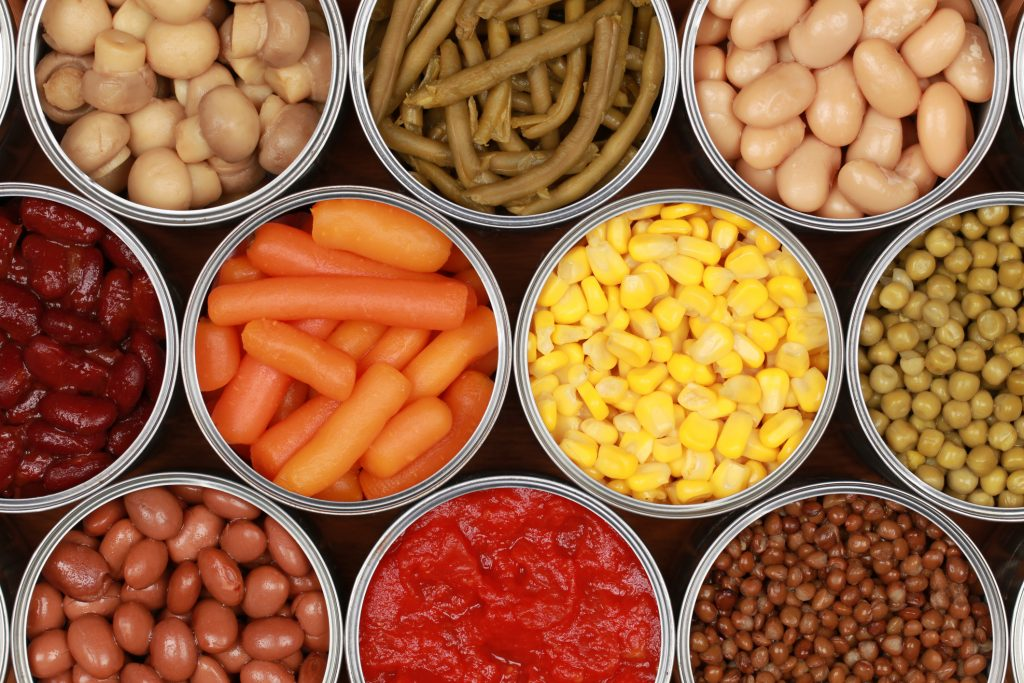Different kinds of vegetables such as corn, peas and tomatoes in cans.