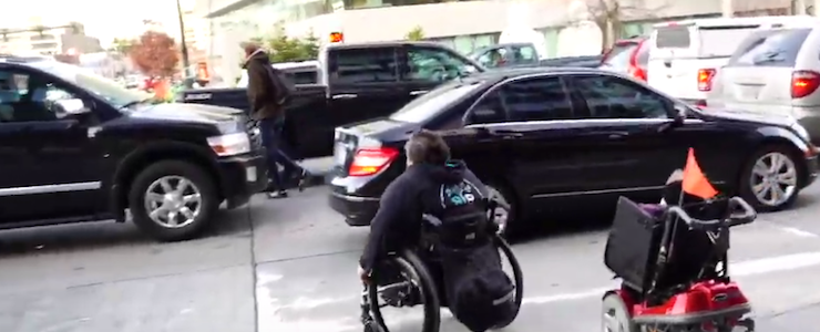 two persons in wheelchairs trying to cross an intersection that's blocked with vehicles in the crosswalk.