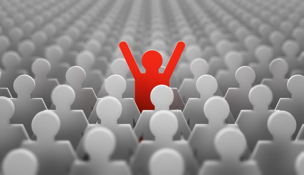 A red paper cut out stick figure raising its arms above a crowd of gray shaded paper cut out people.