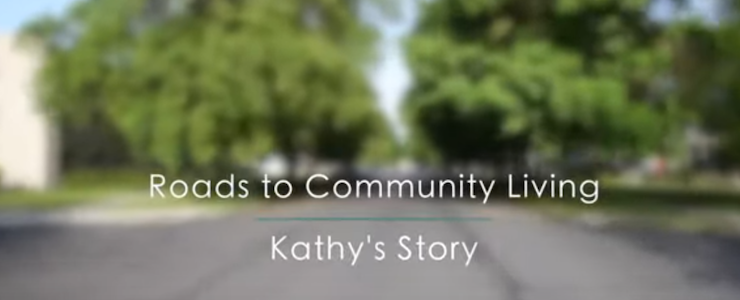 Blurred background of treelined street. Text: Roads to Community Living Kathy's Story.